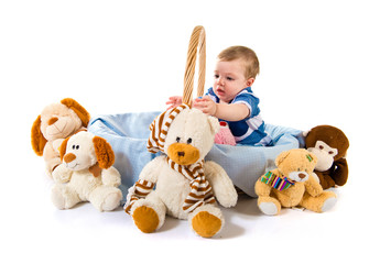 Cute baby inside basket playing with stuffed animals