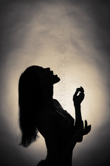 Silhouette of the girl, which pours water.