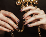 Fototapety close up photo hands with gold manicure holding chain