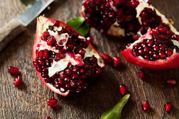 Open fresh ripe pomegranates on wooden background