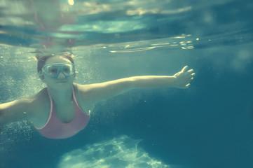 Girl swimming underwater in pool.