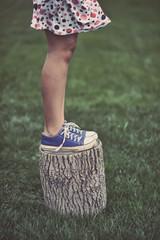 Girl standing on a tree stump