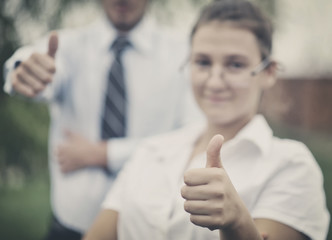 Two young smiling people with thumbs-up gesture