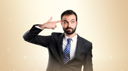 Young businessman committing suicide over white background