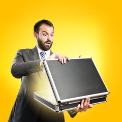 Young businessman open his briefcase over yellow background