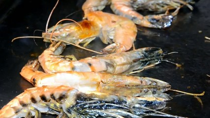Large prawns cooking on a hot plate