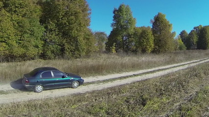 lonely  green car on  rural dirt road . Aerial  view