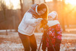 Mother and child set up camera on tripod in rays of setting sun
