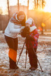 Mother teaches young daughter photographing with tripod sunset