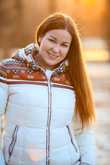 Portrait of attractive smiling woman in down jacket sunlight