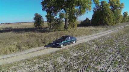 lonely  green car on  rural dirt road . Aerial