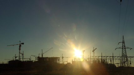 silhouettes of construction and power lines at sunset