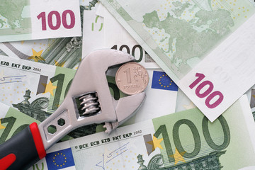 One ruble coin grip in a adjustable wrench on euro banknotes