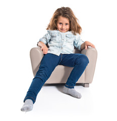 Blonde cute girl sitting on little armchair