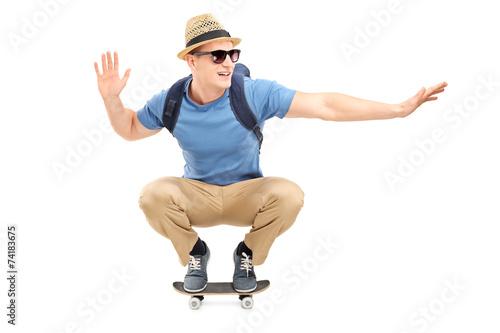 Leinwandbild Motiv Cool young man riding a small skateboard