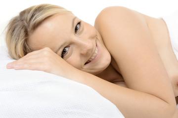 Frau liegt entspannt auf Kissen im Bett