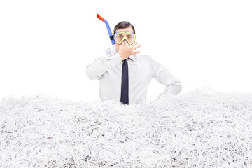 Businessman diving into a pile of shredded paper