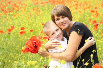 beautiful woman with a child in the spring  field