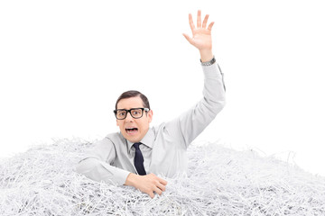 Helpless man drowning in a pile of shredded paper