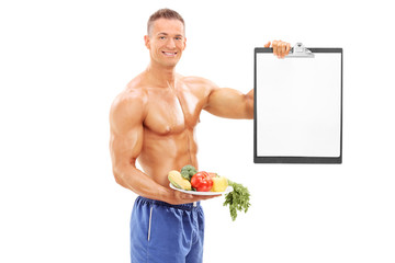 Male athlete holding a plate with vegetables