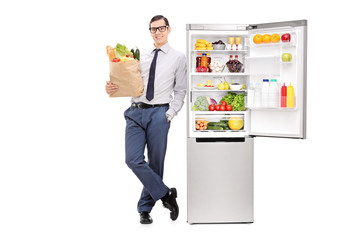 Man holding grocery bag and leaning on a fridge