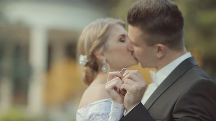 Bride and groom show their wedding rings, kiss and look into