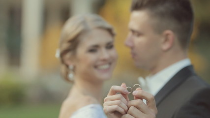 Newlyweds couple in love show their gold wedding rings