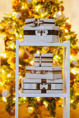 Decorated gift boxes on a shelf near lighting Christams tree