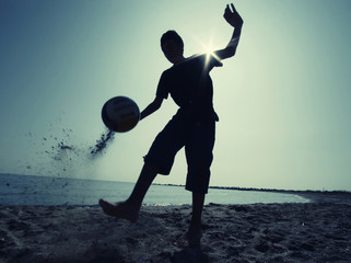 Boy playing football on beach at sunset