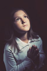 Close up portrait of a little girl praying