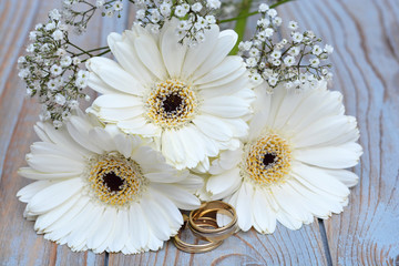 Witte gerbera's met gipskruid en trouwringen