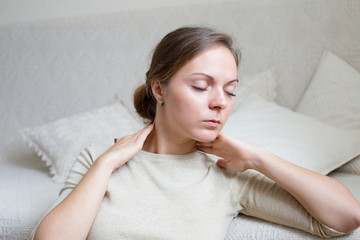 Young woman at home touching her neck in relax mood