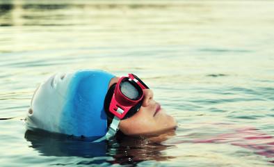 Little girl portrait swimming in sea, close up