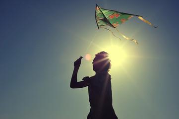 Boy flying a kite on beach at sunrise