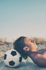Young boy sunbathing on beach, close up