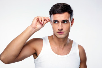 Handsome man removing eyebrow hairs with tweezing