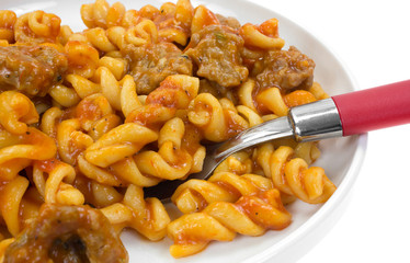 Serving of pasta and sausage on plate with a fork
