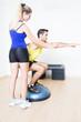 Weiblicher Trainer hilft bei Fitnessuebung