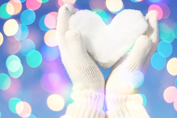 Hands in white gloves holding snow heart