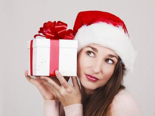 Jeune femme avec un bonnet de noël et un cadeau