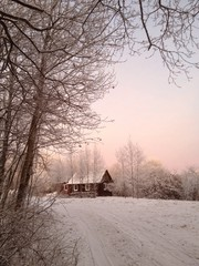 маленький домик в зимнем лесу на закате