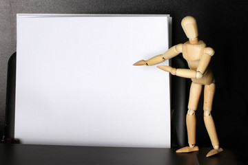 Wooden mannequin points to blank paper