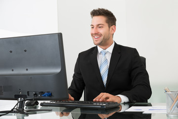 Businessman Using Computer At Desk