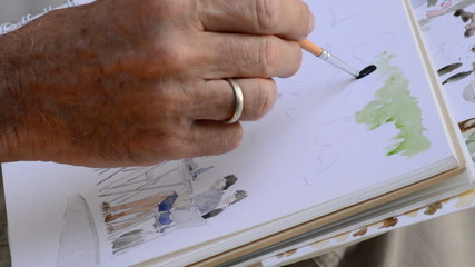 Hand urban sketcher painting a picture
