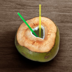 green coconut with cut out heart shape and straws