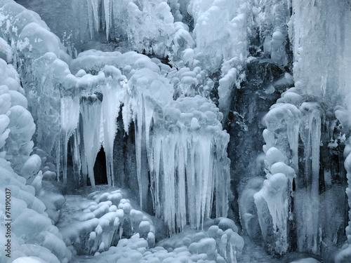 Leinwanddruck Bild A frozen waterfall with ice in winter