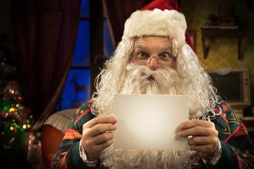 Santa Claus holding a blank card