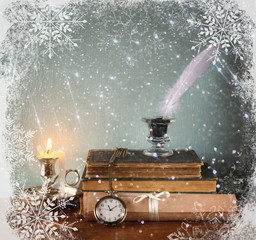 low key image of white Feather, inkwell, old books and candle an