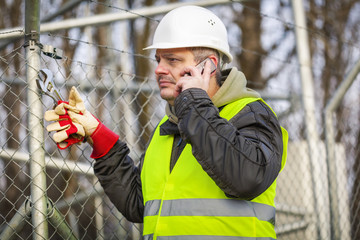 Worker with cell phone and adjustable wrench near fence