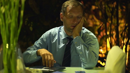 Bored young businessman sitting by table at home at night